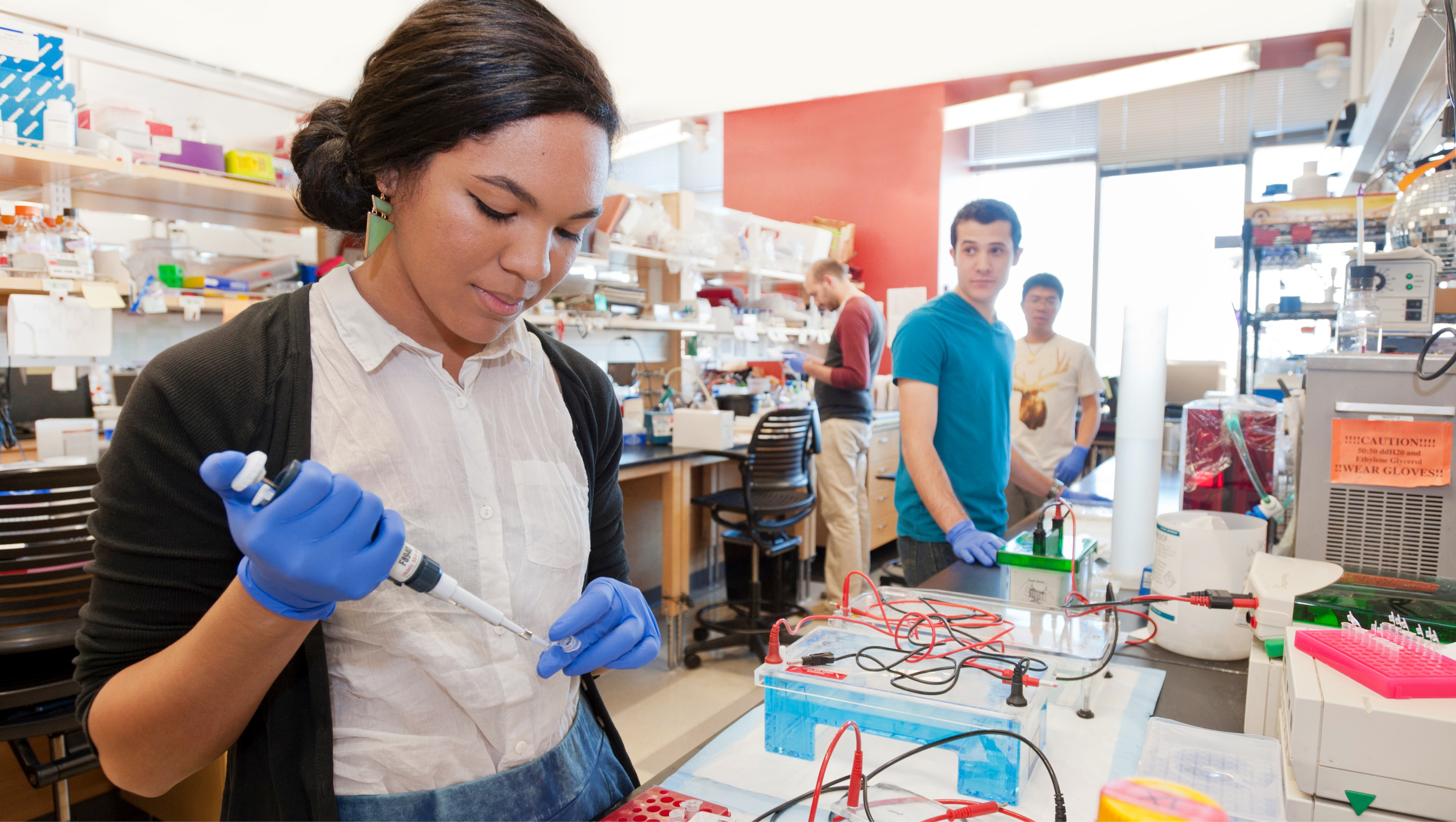 curious student looking over as another student injects some type of liquid into an apparatus