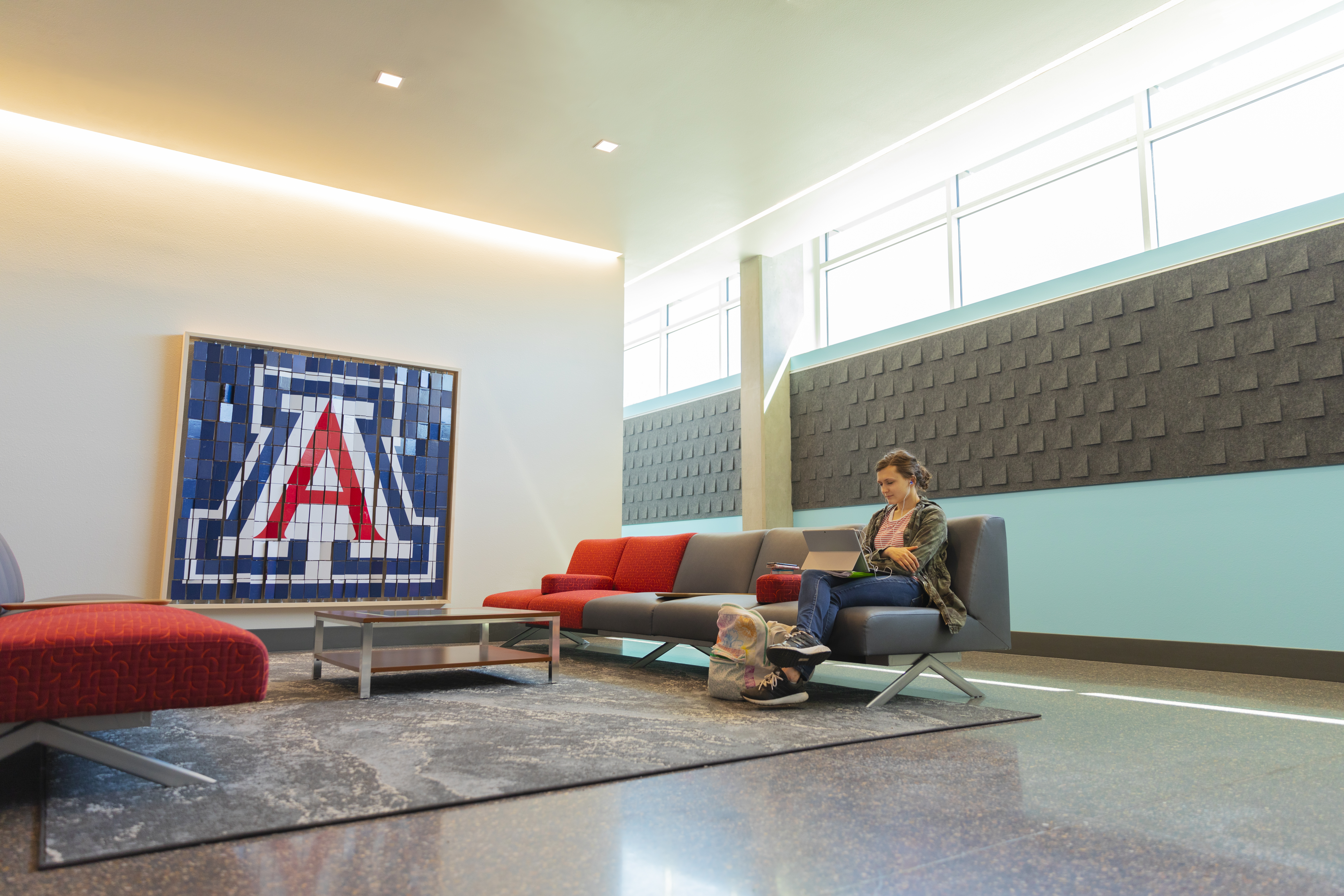 Lounge outside Honors Offices with student on couch