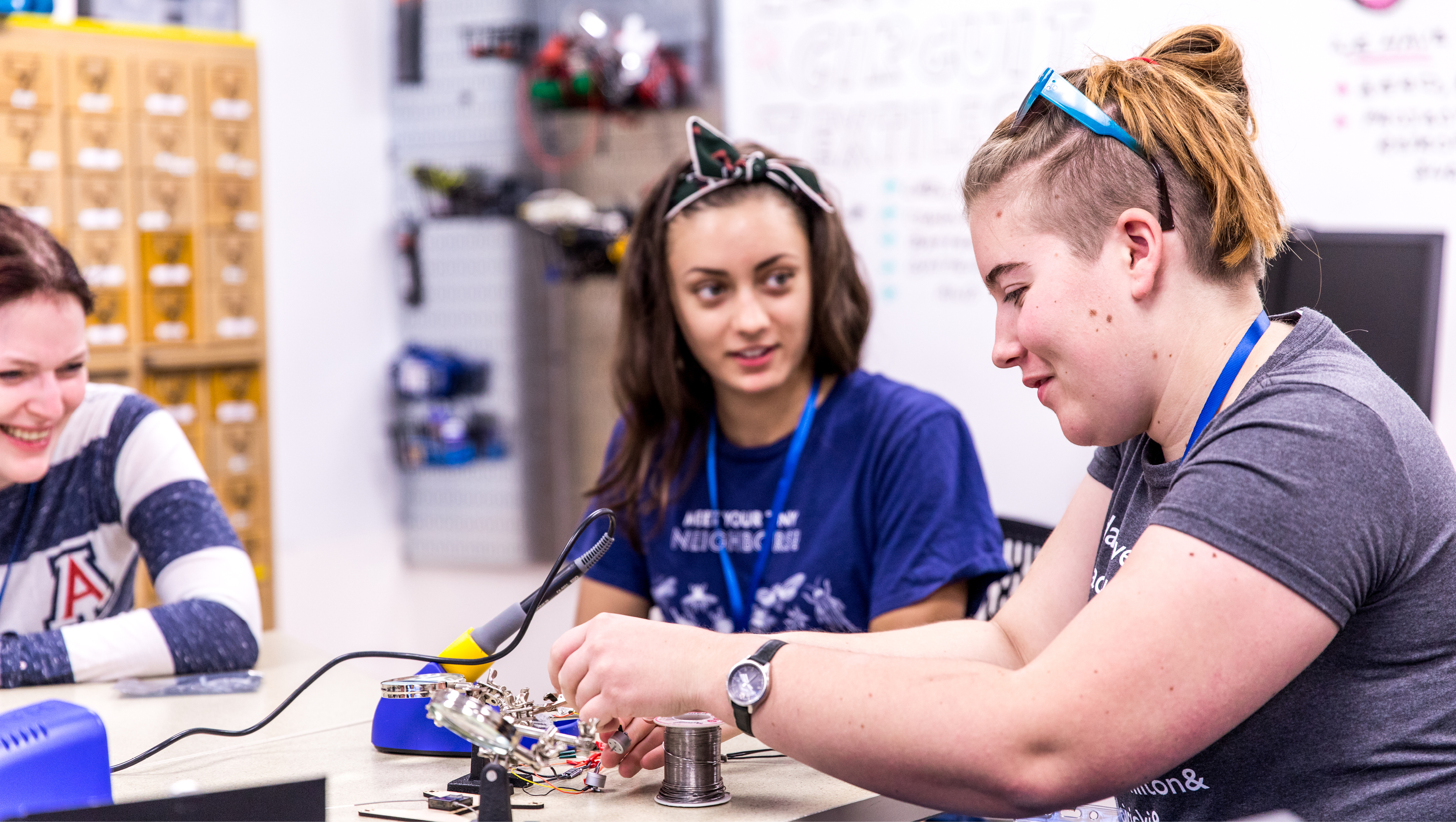 Two students soldering wires