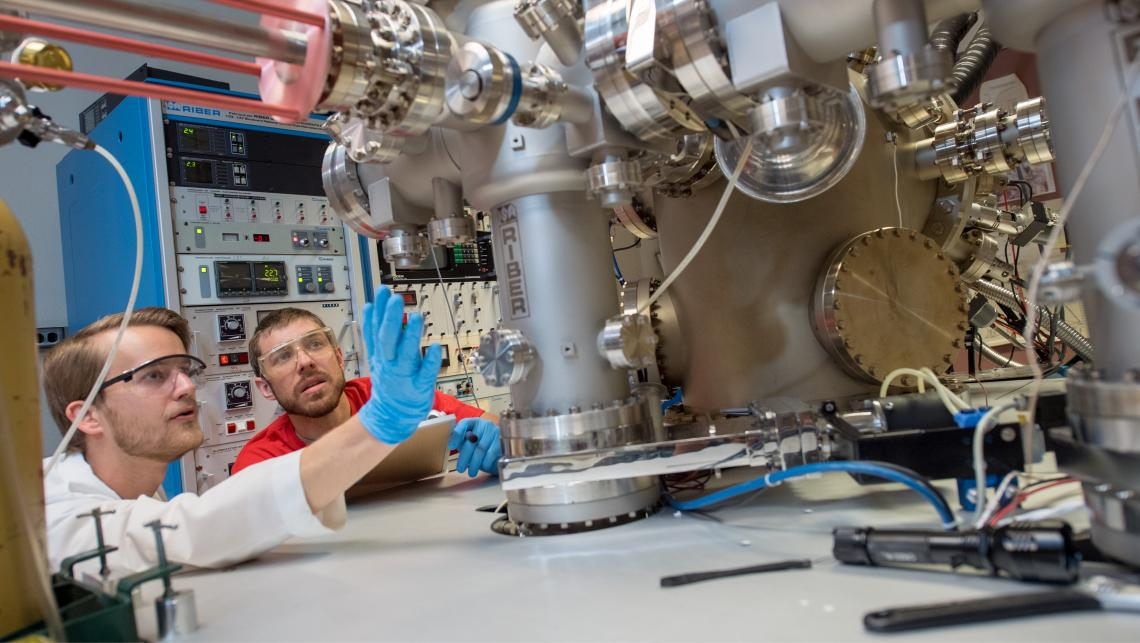 Researchers fiddling with complex machinery