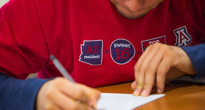 Student in University of Arizona t-shirt writing on a piece of paper
