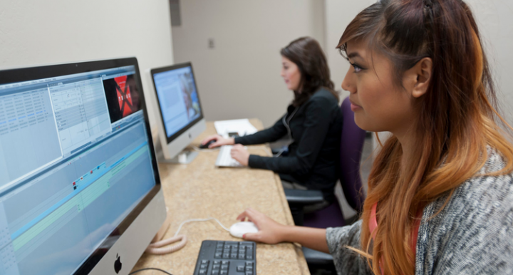 Female student editing video footage on a computer